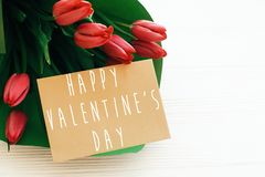 Happy Valentine`s Day text and beautiful red tulips on white wooden background. Happy valentine day greeting card with spring royalty free stock photo