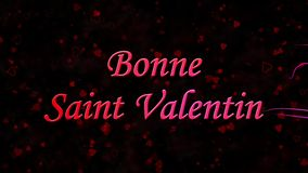 Happy Valentine's Day text in French Bonne Saint Valentin formed from dust and turns to dust horizontally on dark background stock video footage