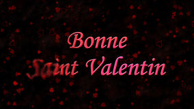 Happy Valentine's Day text in French Bonne Saint Valentin turns to dust from left on dark background Royalty Free Stock Photo