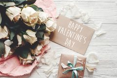 Happy Valentine`s Day text sign on craft greeting card and white roses, gift box on wooden background, flat lay. Valentines day royalty free stock photo