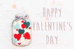 Happy valentine`s day text sign flat lay. cookie hearts in jar a stock photo