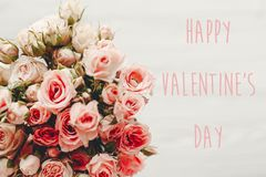 Happy Valentine`s Day text sign on pink roses bouquet on white background, top view. Valentines day floral greeting card royalty free stock photo