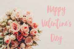 Happy Valentine`s Day text sign on pink roses bouquet on white background, top view. Valentines day floral greeting card royalty free stock image