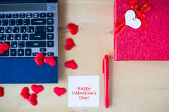 Happy Valentine`s day text written on white stickers, pc, red pen, gift box decorated by red hearts on wooden table in office. Stock Photos