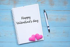 HAPPY VALENTINE`S DAY word on notebook and pen with couple pink heart shape decoration on blue wooden table background. Wedding, royalty free stock photo