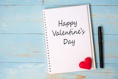 HAPPY VALENTINE`S DAY word on notebook and pen with couple red heart shape decoration on blue wooden table background. Wedding, stock image