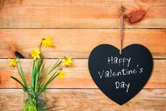 Happy valentine`s day written on a chalkboard in the shape of a heart, daffodils and wood planks background. Happy valentine`s day written on a chalkboard in the stock photo