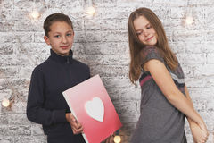 Happy Valentine's Day. Young boy giving a heart picture to his girlfriend Royalty Free Stock Photo
