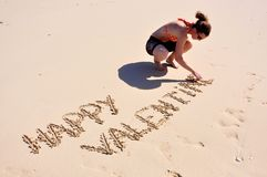 Happy Valentine, woman on beach. Girl crouching on the beach in Dubai, writing happy Valentine Royalty Free Stock Photo