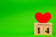 Happy Valentines Day card with red paper heart and wooden calendar. On green background Stock Photos