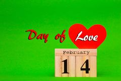 Happy Valentines Day card with red paper heart and wooden calendar. On green background Royalty Free Stock Images