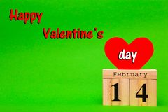 Happy Valentines Day card with red paper heart and wooden calendar. On green background Royalty Free Stock Image