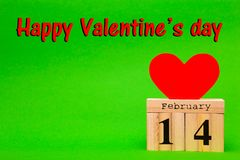 Happy Valentines Day card with red paper heart and wooden calendar. On green background Stock Image