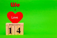 Happy Valentines Day card with red paper heart and wooden calendar. On green background Stock Photo