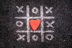 Happy Valentines day card, Tic tac toe game on the ground, xoxo and stone stock photo