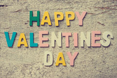 HAPPY VALENTINES DAY. The colorful words HAPPY VALENTINES DAY made with wooden letters on old wooden board Stock Photos