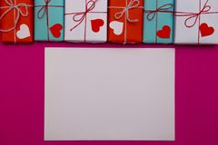 Happy Valentines day composition: white blank of paper with love gift boxes on pink background royalty free stock photography