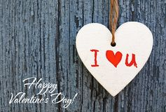 Happy Valentines Day greeting card. Decorative white wooden heart with I love You inscription on a blue wooden background. I Love You,St Valentine`s Day or Love Royalty Free Stock Image