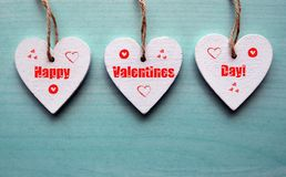 Happy Valentines Day greeting card. Decorative white wooden hearts on a blue wooden background. Royalty Free Stock Images