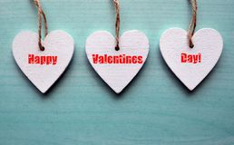 Happy Valentines Day greeting card. Decorative white wooden hearts on a blue wooden background. Stock Photography