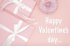 Happy Valentines Day greeting card with pink gift box and sweet donut, ribbon, bow flat lay on living coral color background. stock photo