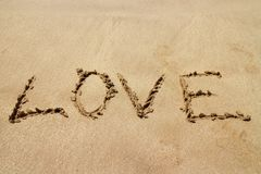 Happy Valentines day, LOVE lettering on the beach with wave and sunlight stock photo