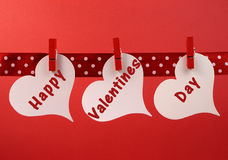 Happy Valentines Day message greeting written across white heart tags hanging from red pegs on a line Stock Photo