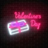 Happy Valentines Day neon glowing festive sign on a dark brick wall background. Gift box with ribbon to beloved person. Holiday greeting card with lettering Stock Photo