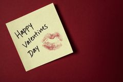 Happy valentines day note on red wall. Lipstick kiss on adhesive note for Valentine's day Stock Photography
