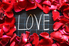 Happy Valentines day! text on blackboard on background of rose petals Royalty Free Stock Photography