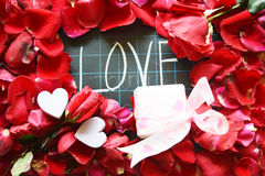 Happy Valentines day! text on blackboard on background of rose petals Stock Photos