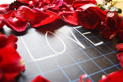 Happy Valentines day! text on blackboard on background of rose petals Royalty Free Stock Image