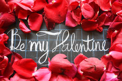 Happy Valentines day! text on blackboard on background of rose petals Stock Photo
