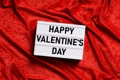 Happy valentines day lightbox on red velvet background royalty free stock images