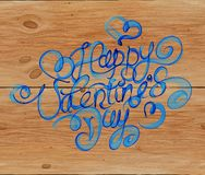 Happy Valentines day vintage lettering written by fire or blue smoke over wooden background.  Stock Photography