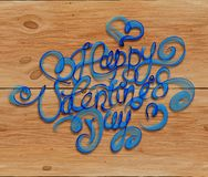 Happy Valentines day vintage lettering written by fire or blue smoke over wooden background.  Royalty Free Stock Image