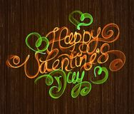 Happy Valentines day vintage lettering written by fire or orange and green smoke over wooden background.  Stock Photography