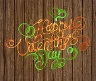 Happy Valentines day vintage lettering written by fire or orange and green smoke over wooden background.  Royalty Free Stock Photo