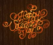 Happy Valentines day vintage lettering written by fire or orange smoke over wooden background.  Stock Photos