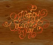 Happy Valentines day vintage lettering written by fire or orange smoke over wooden background.  Royalty Free Stock Photos