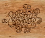 Happy Valentines day vintage lettering written by smoke over wooden background Royalty Free Stock Image