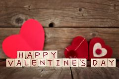 Happy Valentines Day wooden blocks with red hearts against wood Royalty Free Stock Photos