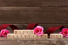 Happy Valentines Day wooden blocks with ribbon and roses Royalty Free Stock Image