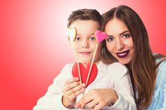 Happy Valentines or mother day. Happy Valentines Day or Mother day. Young boy spend time with his mum and celebrate with gingerbread heart cookies on a stick on royalty free stock image