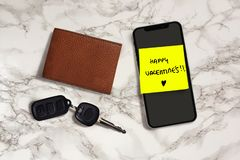 Happy Valentines romantic and sweet handwritten note on yellow posit stick to mobile phone next to car key and leather wallet in stock photo