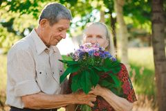 Happy and very old couple smiling in a park on a sunny day. royalty free stock photos