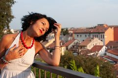 Portrait of a lady on a balcony looking at the city, wearing a white dress, red necklace, wavy dark hair. stock image