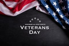 Happy Veterans Day. American flags with the text thank you veterans against a blackboard background. November 11