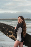 Happy vibe at the beach. Sexy California surfer girl looking over left shoulder at surf break in portrait view Stock Image