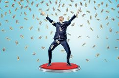 A happy and victorious businessman stands on a giant red button under many falling 100 dollar bills. Stock Photos